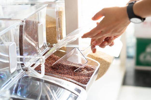 Nahaufnahme, hände der frau schaufeln quinoakörner vom sauberen nachfüllbaren behälter in der schönen nachfüllstation des kleinen geschäfts. gesundes leben, umweltfreundliches und abfallfreies lebensstilkonzept.