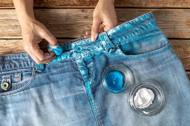 Nahaufnahme hände, die jeans mit farbe färben