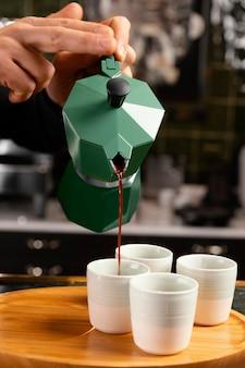 Nahaufnahme hände, die kaffee gießen