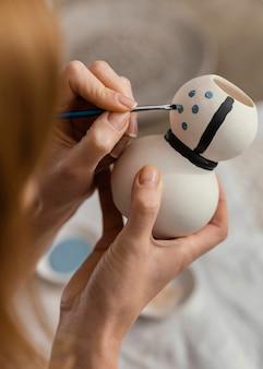 Nahaufnahme hände, die keramikgegenstand malen