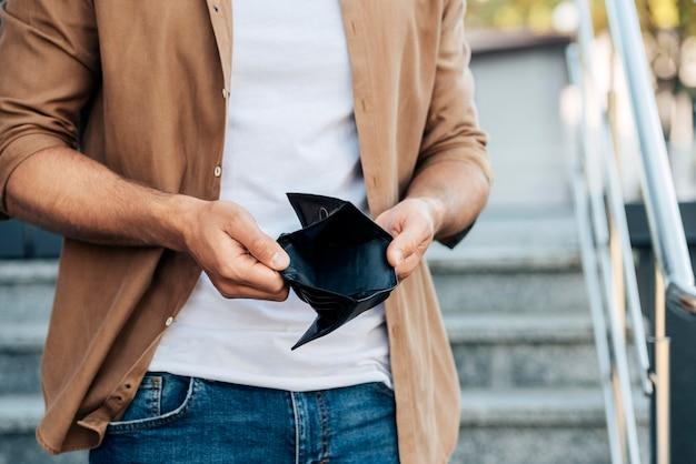 Nahaufnahme hände, die leere brieftasche halten