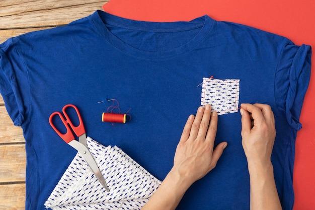 Nahaufnahme hände, die stoff auf hemd nähen