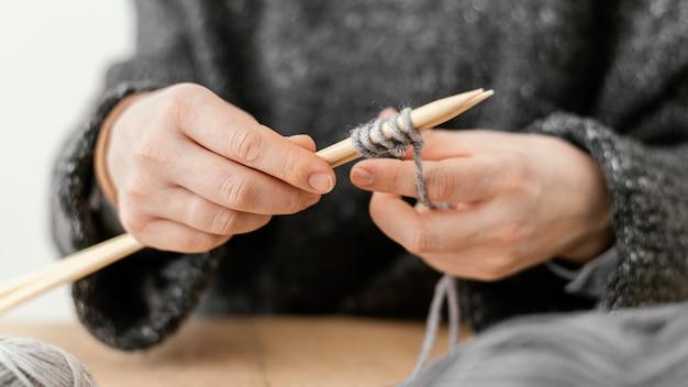 Nahaufnahme hände, die stricknadeln halten