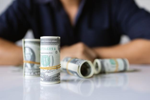 Nahaufnahme hände, die uns dollarnoten mit weichzeichner und über licht im hintergrund halten