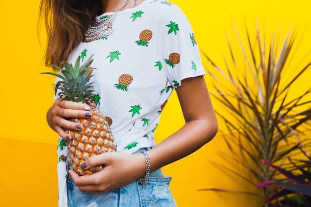 Nahaufnahme hände halten ananas gebräunte haut der attraktiven frau im urlaub tragen strohhut barfuß in denim shorts gedruckt t-shirt sommermode