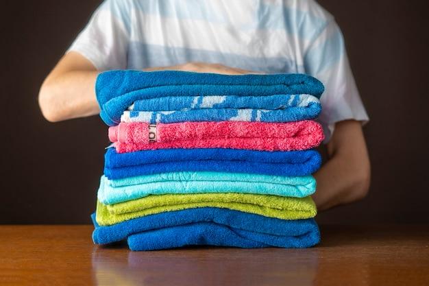 Nahaufnahme hände legen stapel sauberer handtücher auf tisch f