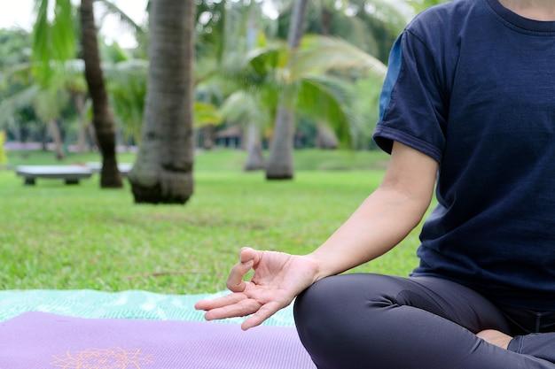 Nahaufnahme halber körperteil einer asiatischen frau, die yoga-praxis im öffentlichen parklebensstil und gesund spielt