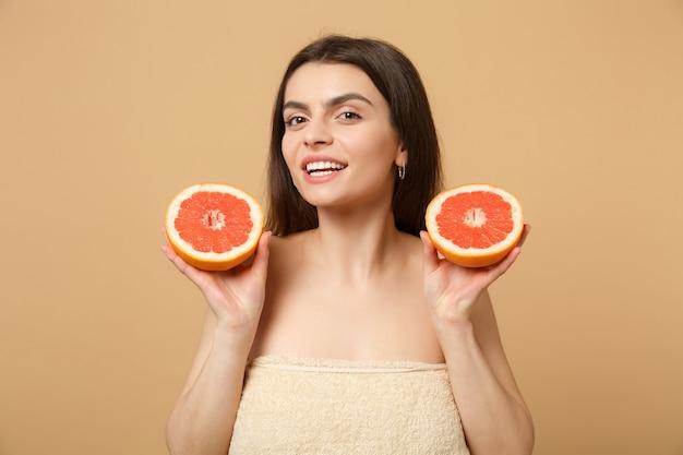 Nahaufnahme halbnackte frau mit perfekter haut nackt make-up hält grapefruit isoliert auf beige pastellfarbener wand
