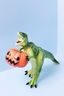 Nahaufnahme halloween-dinosaurierspielzeug, das kürbis hält