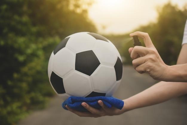 Nahaufnahme hand alkohol spray reinigung fußball sind neu normal und football league kommen zurück