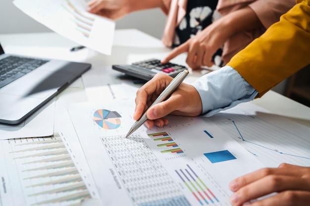 Nahaufnahme hand buchhalter hält stift zeigt auf papierkram diagramm für besprechungsteam im büroraum. konzept finanz- und rechnungswesen