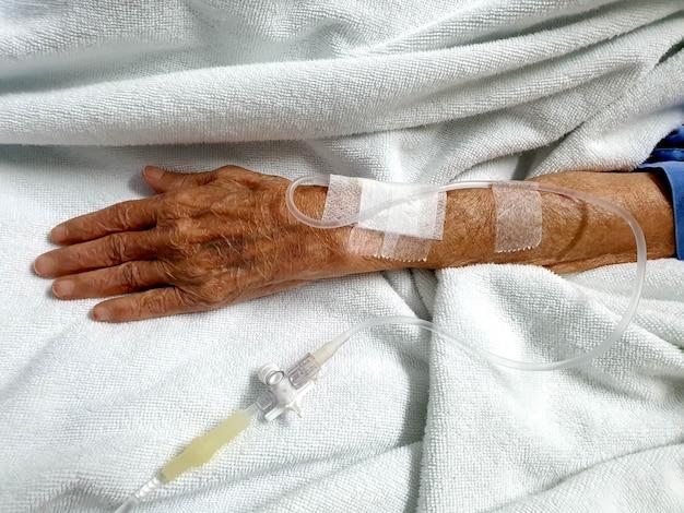 Nahaufnahme hand der alten patientin kochsalzlösung im krankenzimmer