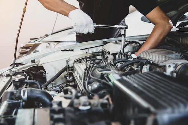 Nahaufnahme hand des automechanikers verwendet schraubenschlüssel, um einen automotor zu reparieren