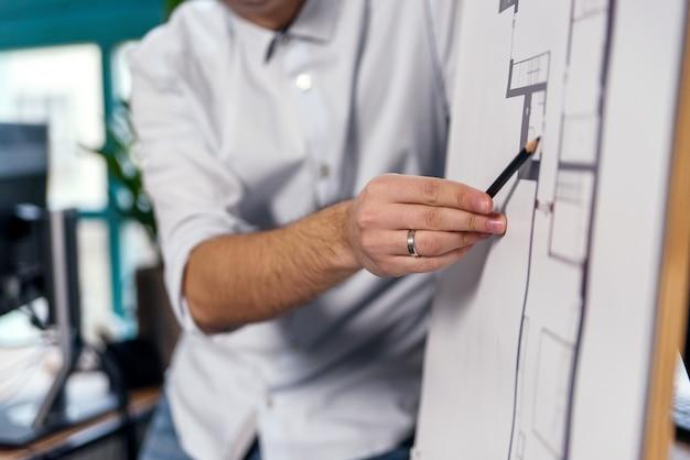 Nahaufnahme hand des jungen firmenleiters mit bleistift erklärt arbeitsaufgaben für seine mitarbeiter.