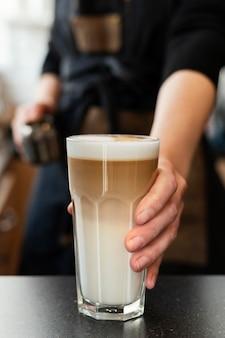 Nahaufnahme hand, die cafe latte hält