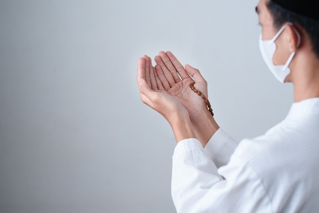 Nahaufnahme hand, die eine muslimische perlen oder tasbih mit auf grau hält