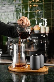 Nahaufnahme hand, die kaffee gießt