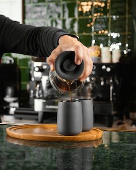 Nahaufnahme hand, die kaffee in tasse gießt