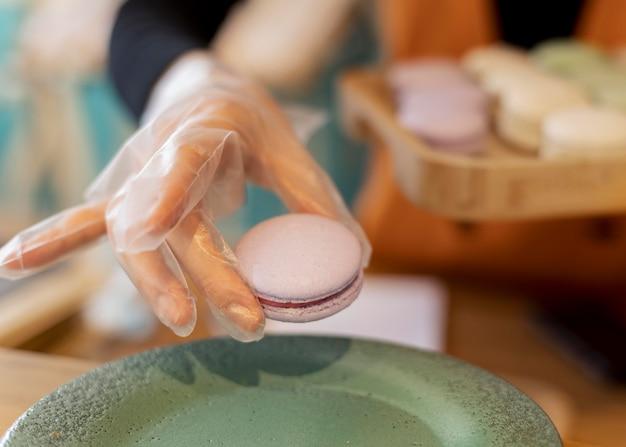 Nahaufnahme hand, die macaron hält