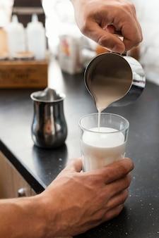 Nahaufnahme hand, die milch in glas gießt