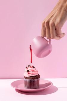 Nahaufnahme hand, die rosa sirup gießt