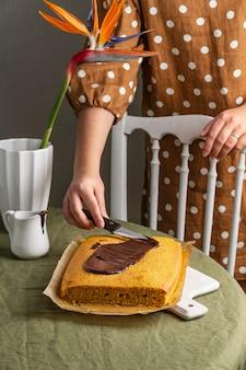 Nahaufnahme hand, die schokolade auf kuchen verteilt
