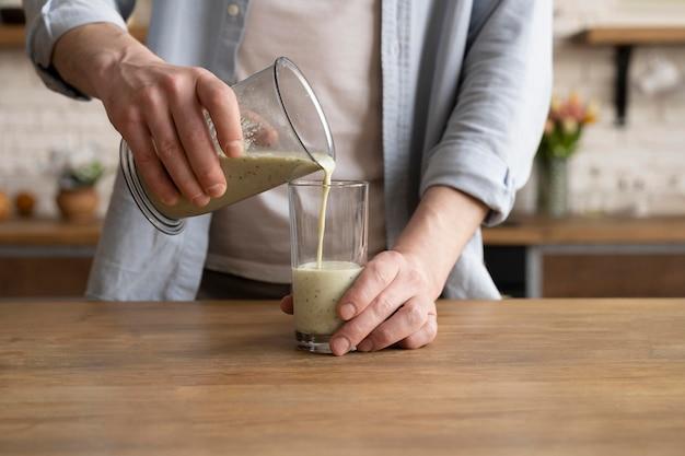 Nahaufnahme hand, die smoothie in glas gießt