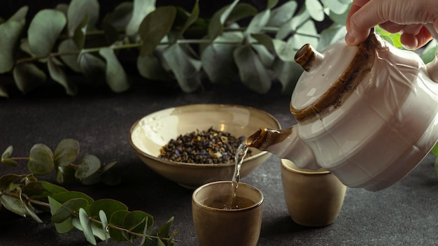 Nahaufnahme hand, die tee in tasse gießt
