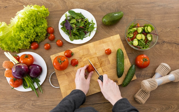 Nahaufnahme hand, die tomatenoberansicht schneidet