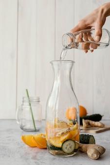 Nahaufnahme hand, die wasser in flasche gießt