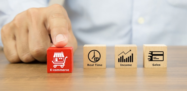 Nahaufnahme hand, die würfelholzspielzeugblöcke mit franchise-geschäft und e-commerce-symbol wählt.