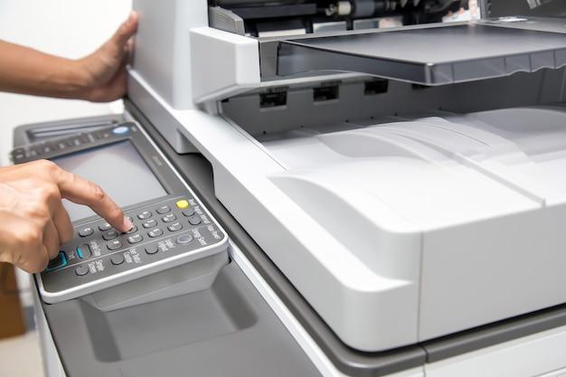 Nahaufnahme hand drücken taste, um den fotokopierer zu verwenden.