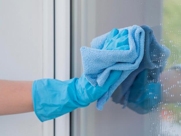 Nahaufnahme hand mit gummihandschuh reinigungsfenster