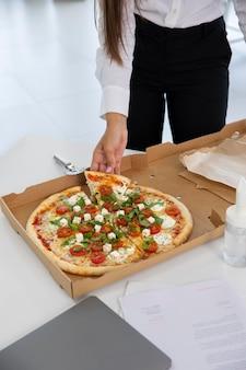 Nahaufnahme hand mit pizzastück