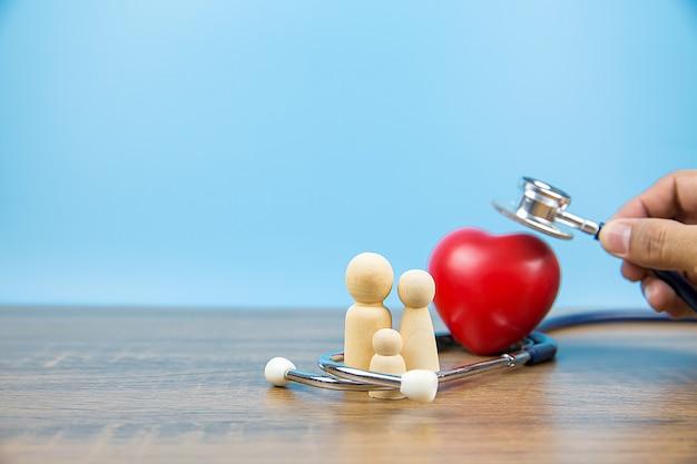 Nahaufnahme hand mit stethoskop prüft ein herz mit familiensymbol.