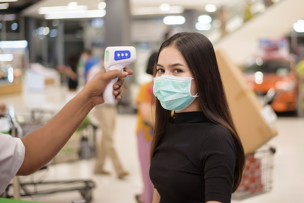 Nahaufnahme hand mit temperaturpistole mit junger frau, soziale distanzierungsmaßnahme für die covid-19-prävention im einkaufszentrum