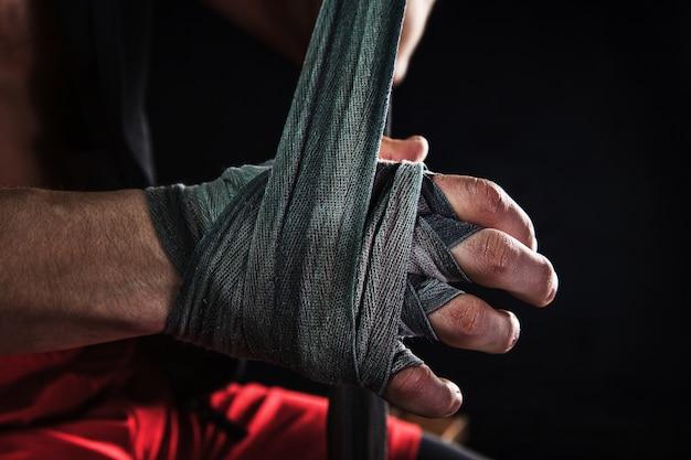 Nahaufnahme hand mit verband des muskulösen mannes, der kickboxen auf schwarz trainiert