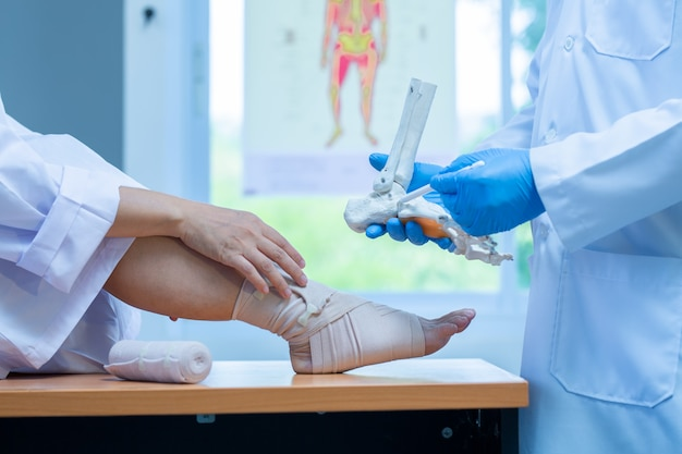 Nahaufnahme hand tragen medizinische handschuhe arzt in medizinischen handschuhen hält künstlichen knochen des fußes und untersucht ein schmerzendes bein mit einem fersensporn auf einer frau, nahaufnahme, osteophyten und ferse, faszie
