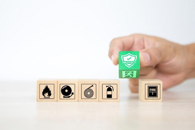 Nahaufnahme hand wählen holzklötze mit schutz und türausgang symbol gestapelt.