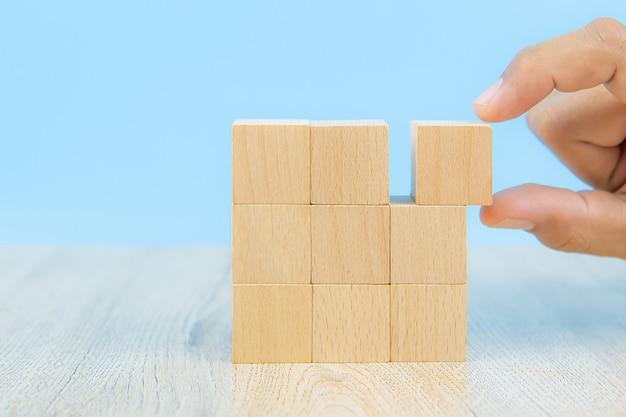 Nahaufnahme hand wählen sie eine würfelförmige holzblock spielzeug ohne grafiken gestapelt.