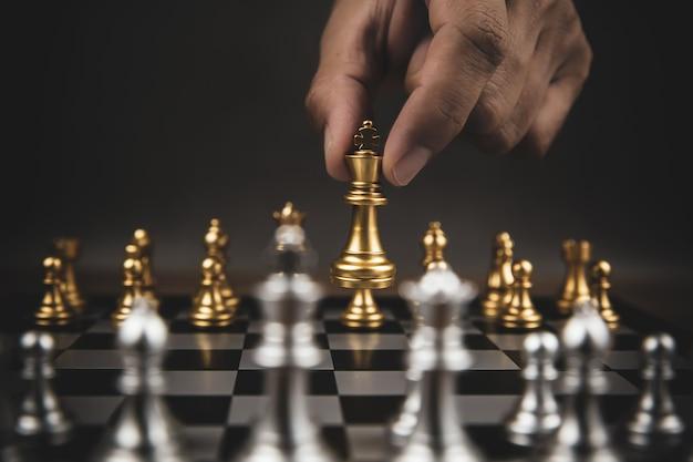 Nahaufnahme hand wählen sie goldschach, um mit dem silve-schachteam auf dem schachbrett herauszufordern.