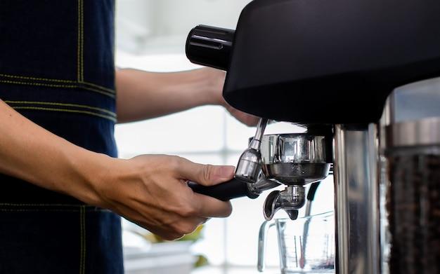 Nahaufnahme hand warmes wasser in ein glas geben. zubereitung einer tasse kaffee in einer kaffeemaschine, dampf und tasse. espressomaschine mit siebträger hautnah. konzept-kaffeemaschine im café.