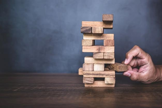 Nahaufnahme hand ziehen holzblock von anderen holzblock in turmform gestapelt.