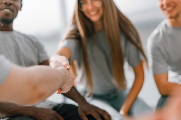 Nahaufnahme. handschlag junger menschen während eines business-seminars. wirtschaft und bildung