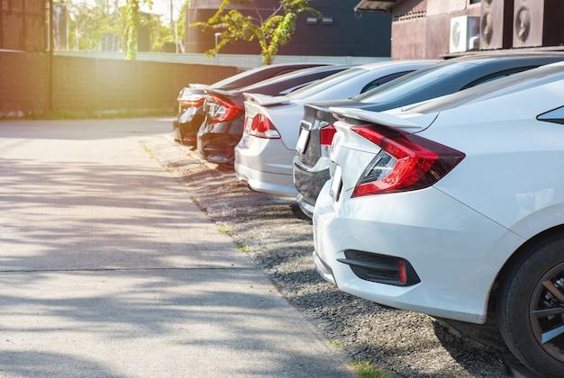 Nahaufnahme hinten des weißen modernen autos mit schwarzem kofferraum der reihe von autos und lieferwagen, die auf asphalt am hellen sonnigen tag geparkt werden. transport- und parkkonzept.