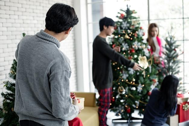 Nahaufnahme hinter dem jungen mann, der weihnachtsbäume der weihnachtsfeier mit freundenhintergrund verziert. feiern des neuen jahres. frohe weihnachten und schöne feiertage.