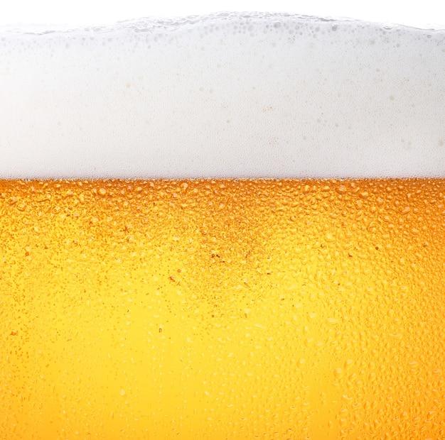 Nahaufnahme hintergrund des gießens von lagerbier mit blasen und schaum in frostigem glas mit tropfen
