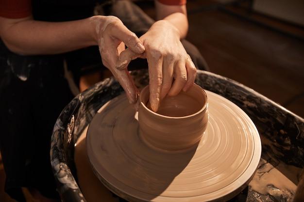 Nahaufnahme hintergrund von eleganten weiblichen händen, die ton auf einer töpferscheibe formen, die von sonnenlicht beleuchtet wird, kopienraum