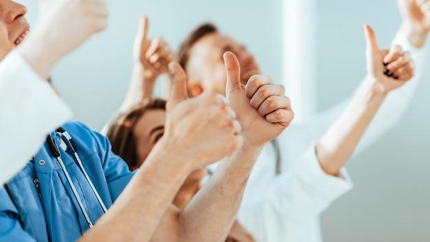 Nahaufnahme. hintergrundbild einer gruppe von ärzten, die daumen nach oben zeigen. foto mit textfreiraum