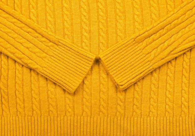 Nahaufnahme hintergrundtextur von warmen gelben kabel gestrickter wolljersey-stoffpullover mit reihengeflechtmuster